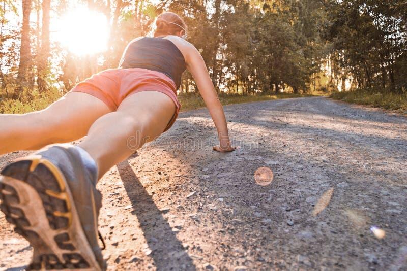 Junge Sportfrau tut Liegestütze lizenzfreies stockfoto