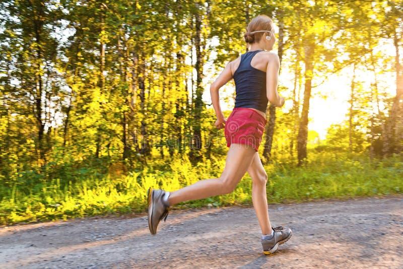 Junge Sportfrauenläufe auf der Straße lizenzfreie stockfotos