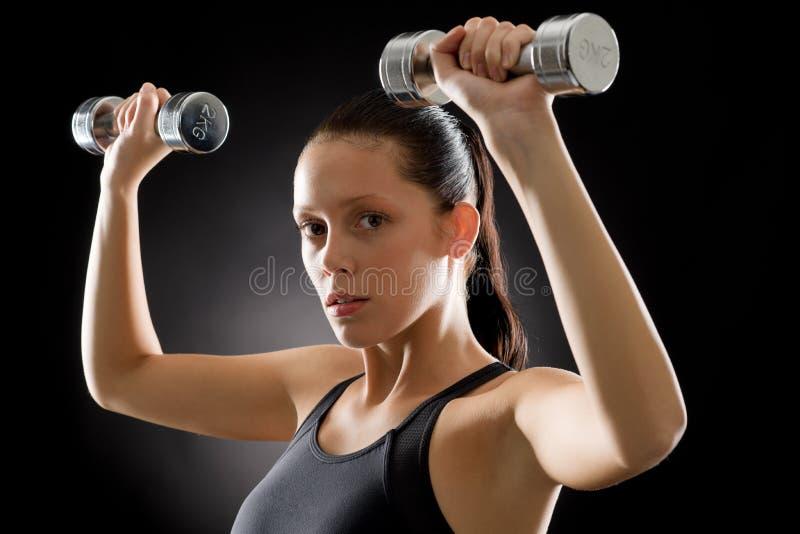 Junge sportive Gewichtsübung der Eignungsfrau stockfotos