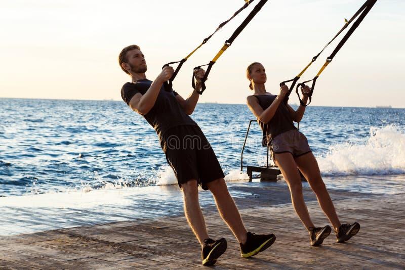 Junge sportive Leute, die morgens mit trx nahe Meer ausbilden stockfotos