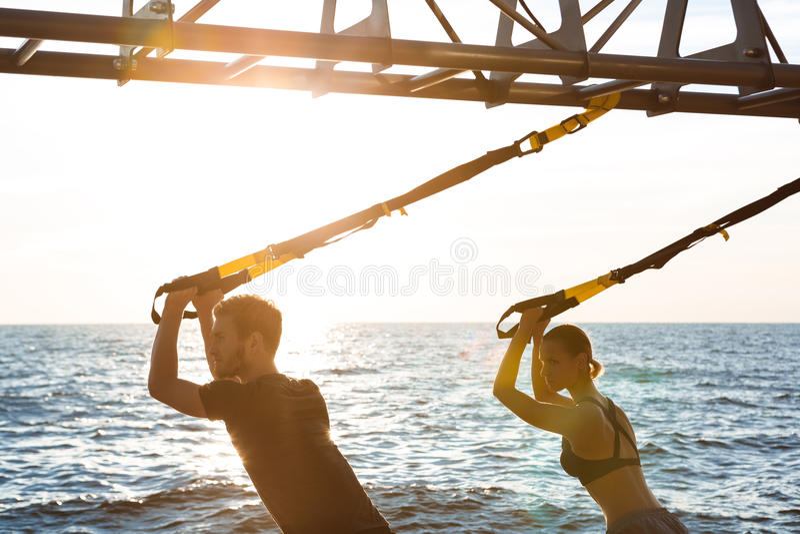 Junge sportive Leute, die morgens mit trx nahe Meer ausbilden stockbild