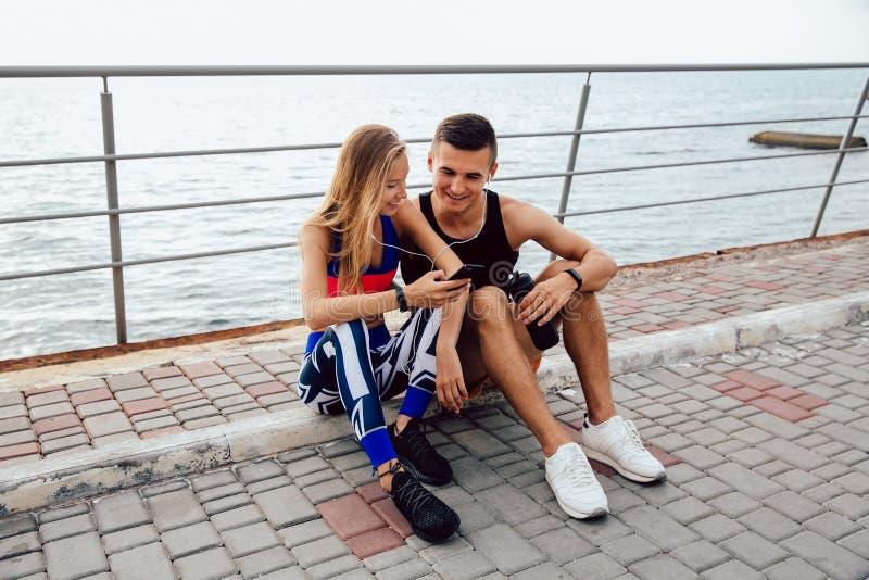 Junge sportive Paare, die ein Video am Handy, beim Sitzen aus den Grund aufpassen lizenzfreie stockfotos