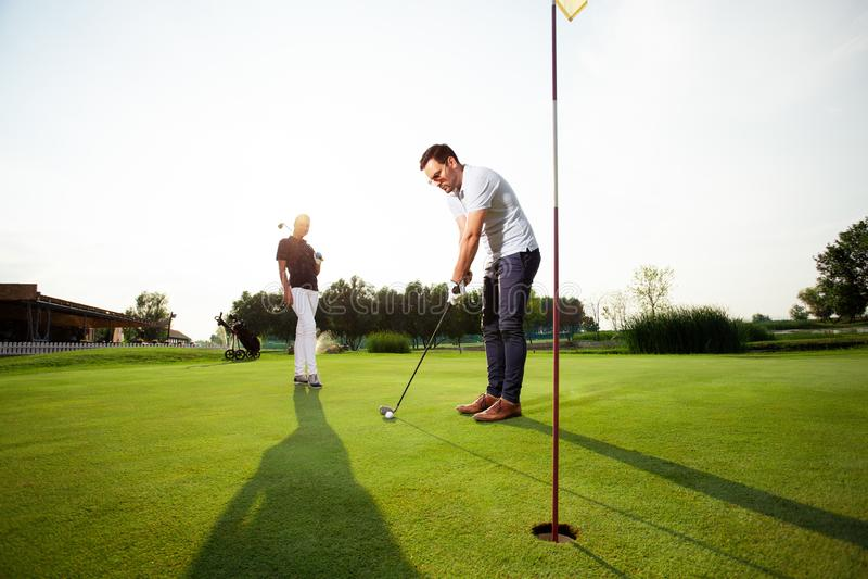 Junge sportive Paare, die Golf auf einem Golfplatz - Bild spielen stockfotografie