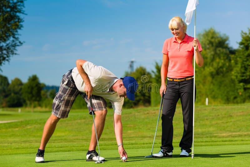 Junge sportive Paare, die Golf auf einem Kurs spielen lizenzfreies stockfoto
