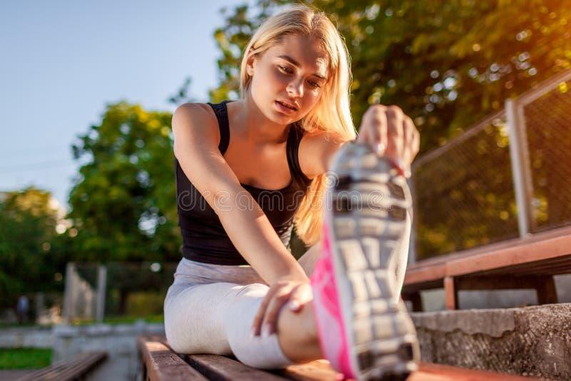 Junge Sportlerin, die bevor dem Laufen auf sportsground im Sommer aufwärmt Ausdehnen des Körpers stockfotos