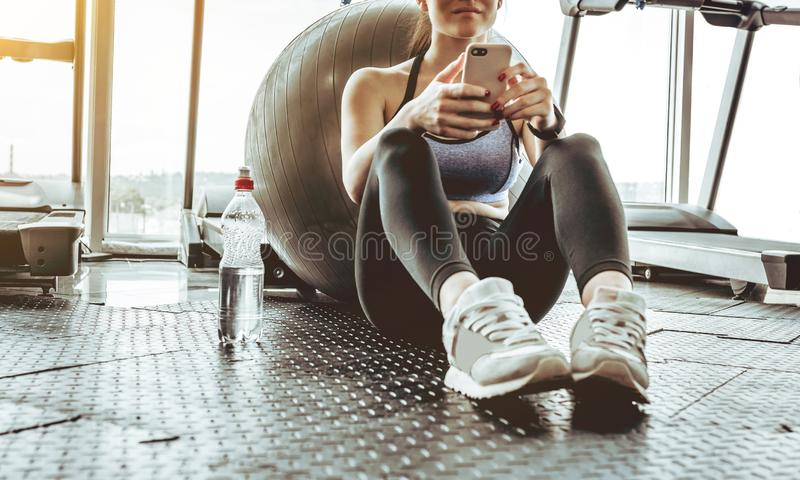 Junge Sportlerin, die Handy an der Turnhalle verwendet stockbild