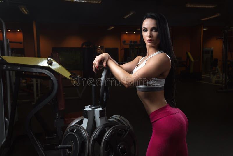 Junge Sportlerin ist, aufwerfend stillstehend und nach Übungen mit Gewichtsplatte stockbilder