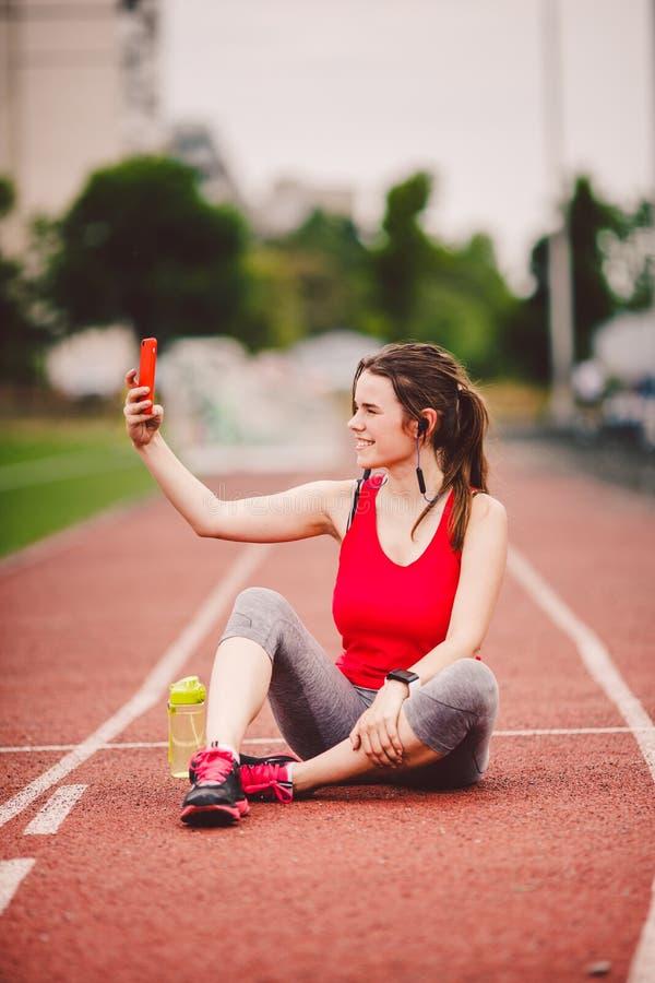 Junge Sportlerin am zur Schau tragenden Lebensstil des Stadions, sitzend auf der Bahn und machen selfie Foto auf einem Smartphone lizenzfreies stockfoto