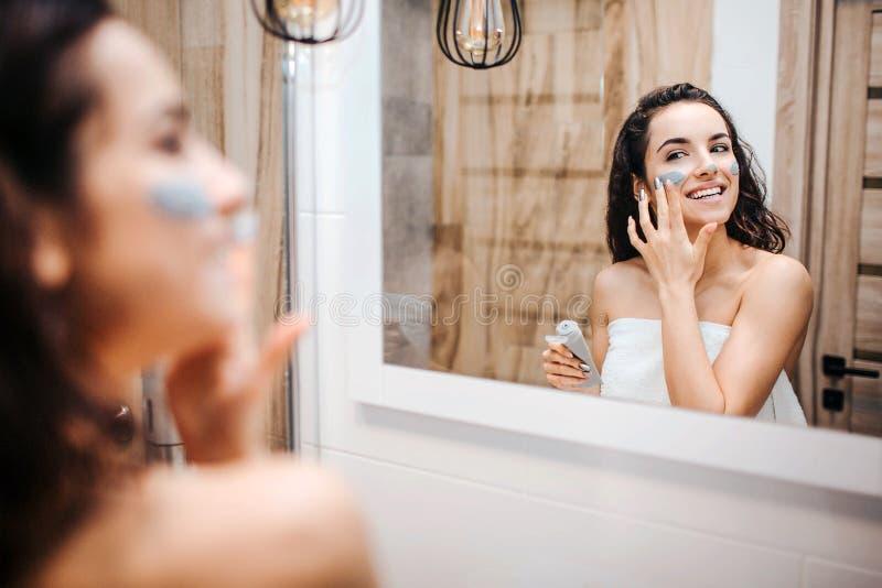 Junge sportliche dunkelhaarige Schönheit, die Morgen Abendprogramm am Spiegel tut Nettes glückliches Modell eingewickelt im Weiß lizenzfreie stockfotografie