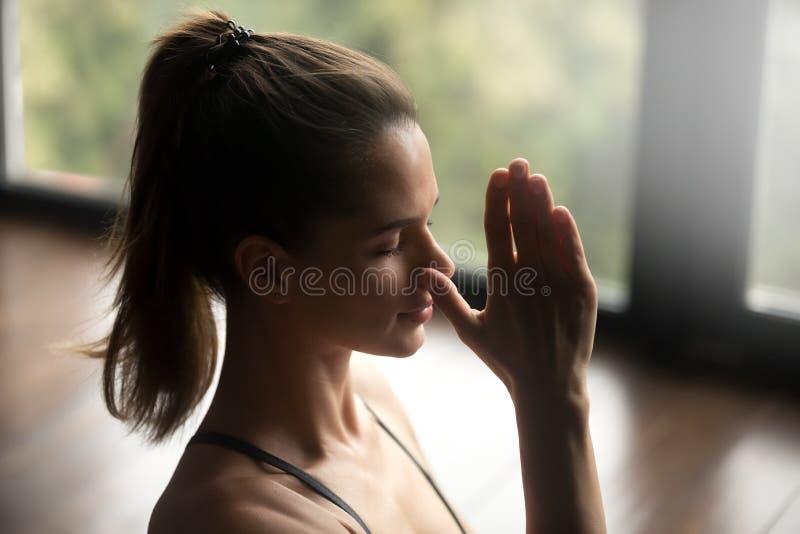 Junge sportliche Frau in der abwechselnden Nasenloch-Atmung stockfoto