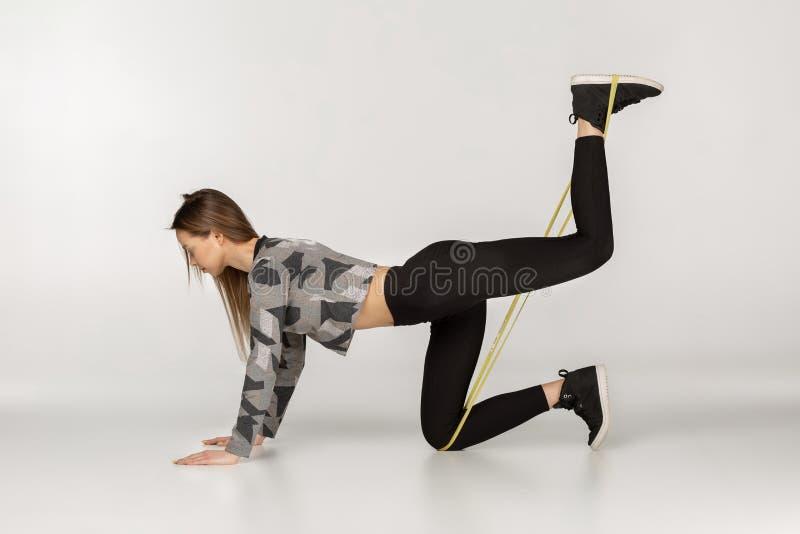 Junge sportliche Frau, die Übungen mit Gummiband tut lizenzfreie stockbilder