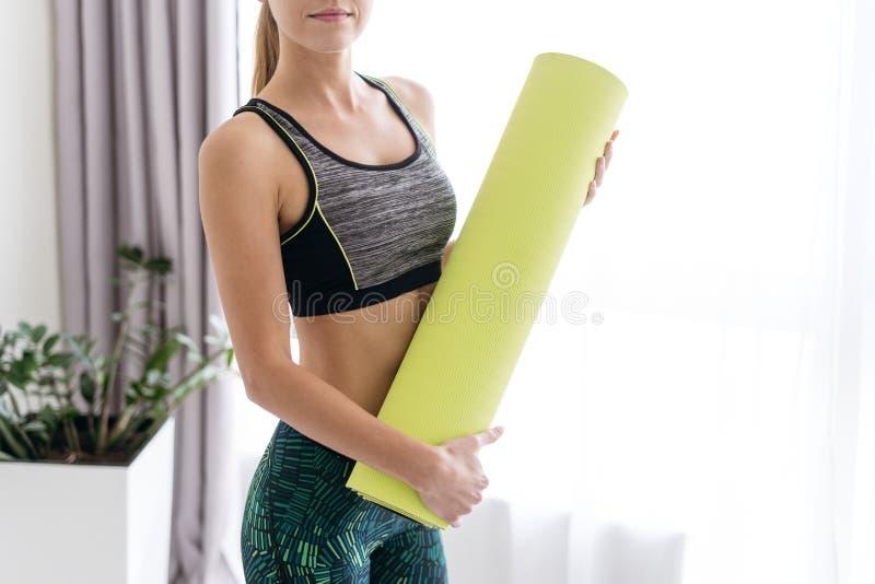 Junge sportliche Frau, die Eignungsmatte in den Händen hält lizenzfreies stockfoto