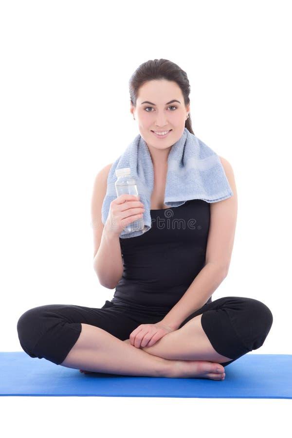 Junge sportliche Frau, die mit der Flasche Mineralwasser lokalisiert sitzt lizenzfreies stockbild