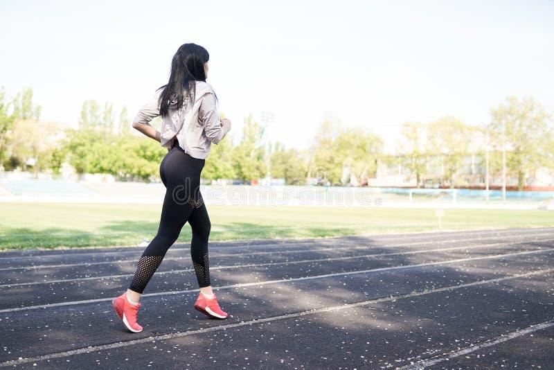 Junge sportliche Frau, die morgens läuft Nette gl?ckliche und ?berzeugte Eignungfrau, die an der Kamera l?chelt Sporthintergrund  lizenzfreies stockfoto