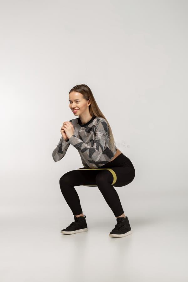 Junge sportliche Frau, die SitzenUPS mit Widerstandband tuend hockt lizenzfreie stockfotografie
