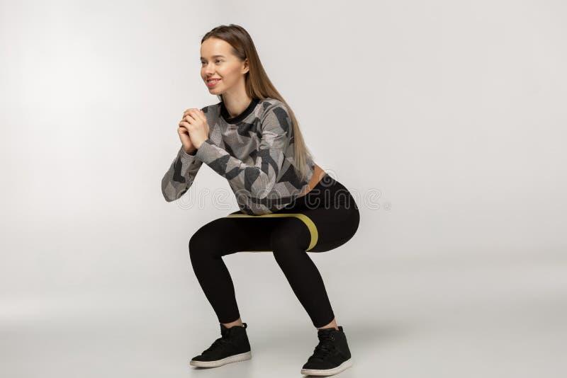 Junge sportliche Frau, die SitzenUPS mit Widerstandband tuend hockt stockbild
