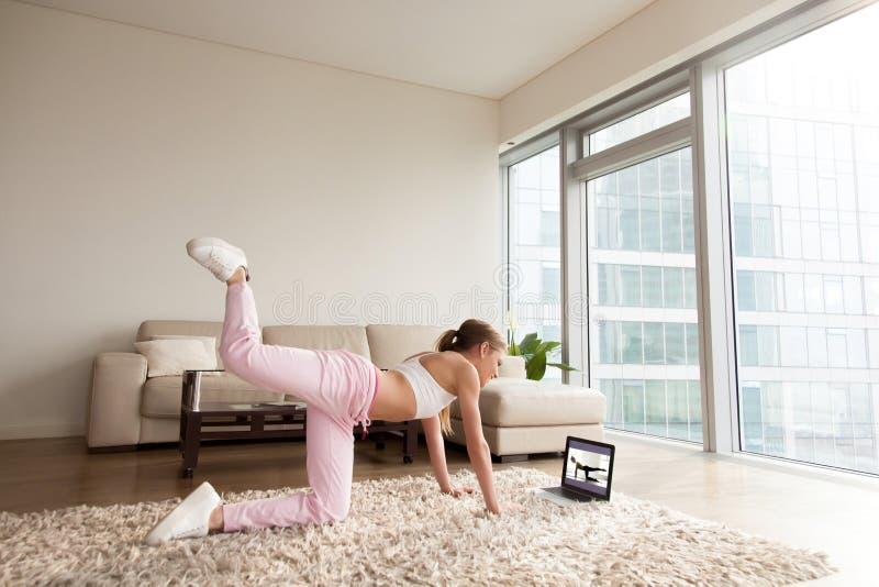 Junge sportliche Frau, die zu Hause, on-line-Eignungstraining ausarbeitet stockbild