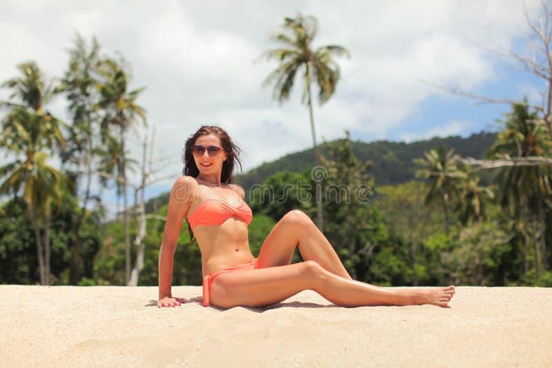 Junge sportliche Frau im orange Bikini und in der Sonnenbrille, sitzend auf dem Sand nahe Strand, Palmen hinter ihr lizenzfreie stockfotos