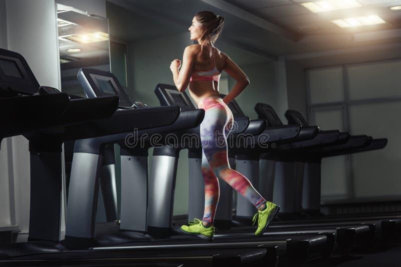 Junge sportliche Frau laufen auf Maschine in der Turnhalle lizenzfreie stockfotografie