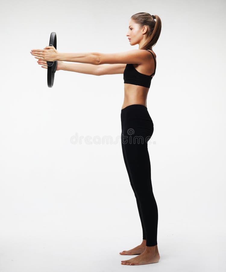 Junge sportliche Frau mit dem perfekten Körper, der ein Training mit pila hat lizenzfreie stockfotografie