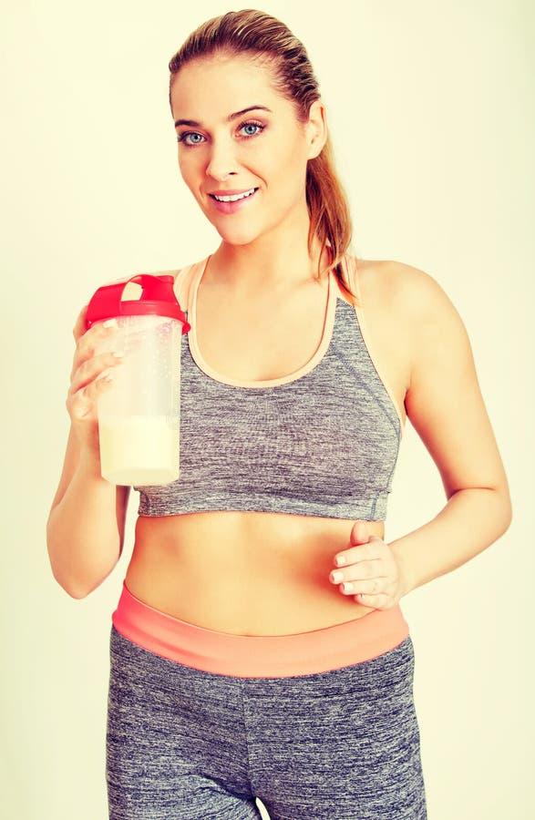 Junge sportliche Frau mit Proteindrinkflasche stockfotos