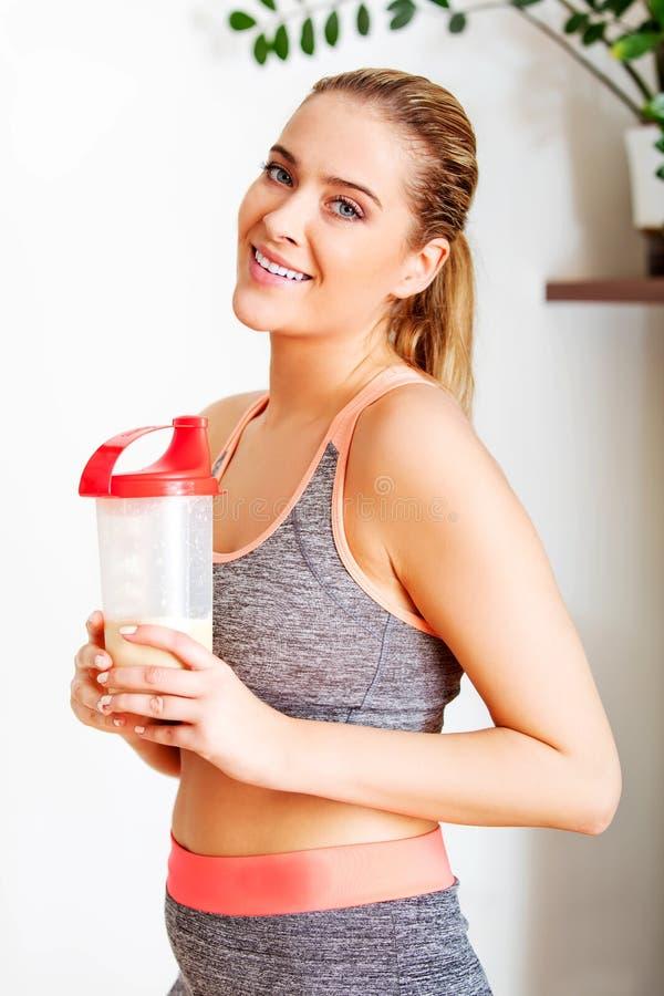 Junge sportliche Frau mit Proteindrinkflasche lizenzfreie stockbilder
