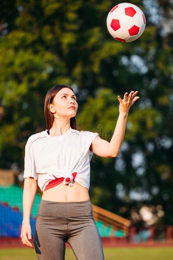 Junge sportliche Frau wirft oben Fußball stockfotos