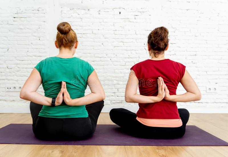 Junge sportliche Freundinnen, die das Yoga zusammen macht Namaste hinter der Rückseite im gesunden Leben üben lizenzfreie stockfotografie