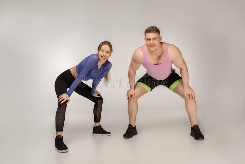 Junge sportliche Paare in der bunten Sportkleidung, die nach der Ausbildung stillsteht stockfotos