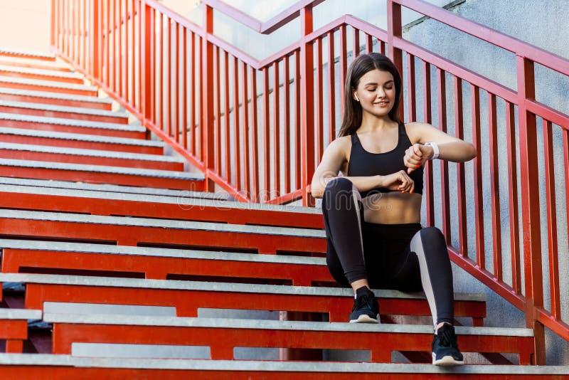 Junge sportliche Schönheit, die einen Bruch sitzt auf der roten Treppe nach dem Morgen rüttelnd in der modernen Stadt, überprüfen lizenzfreies stockbild