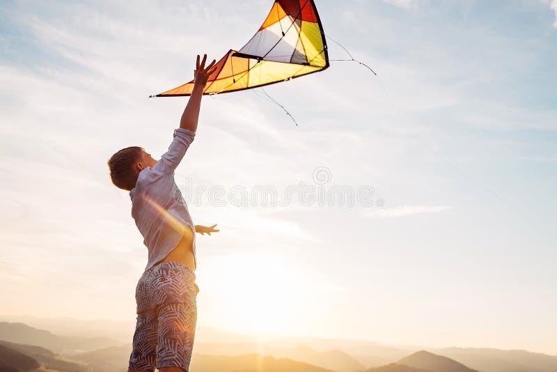 Junge springt und strats, um einen Drachen im Himmel zu fliegen stockbilder