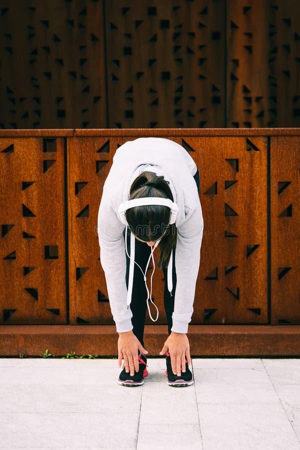 Junge städtische Eignungsfrau, die Kniesehnen ausdehnt stockbilder