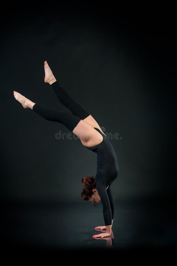 Junge starke Frau in der athletischen Fähigkeit der Turneranzugs-Show auf Schwarzem stockfoto