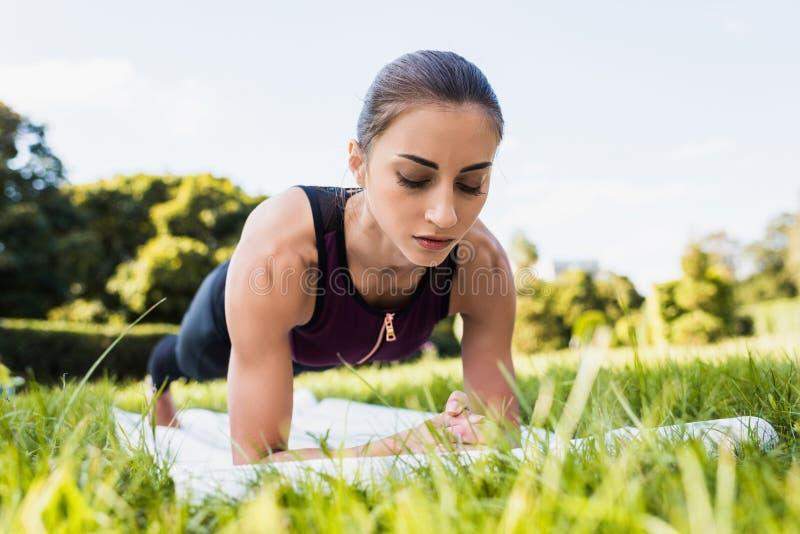junge starke Frau, die Planke auf Graswiese tut lizenzfreies stockbild