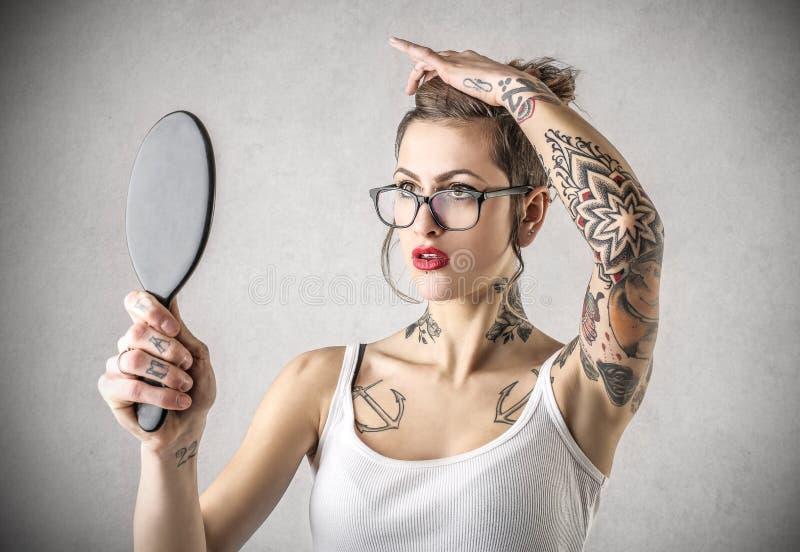 Junge starke frau mit den t towierungen die einen spiegel for Spiegel kinderzimmer junge