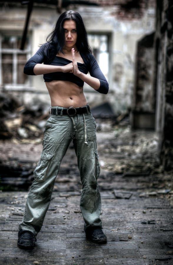 Junge starke Frau in ruiniertem Gebäude lizenzfreie stockfotografie