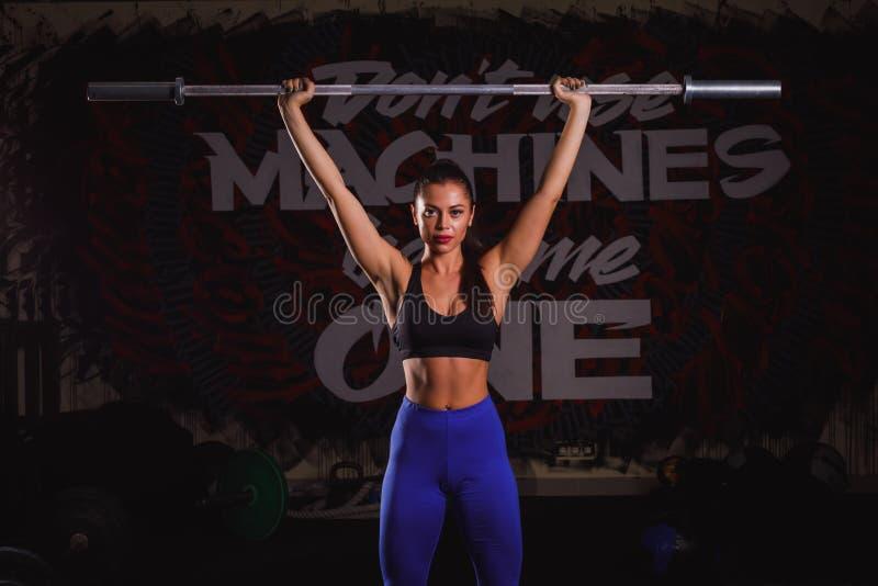 Junge starke kaukasische Sportfrau, die mit Stange aufwirft Mädchen führen Übung mit Barbell durch stockfotos