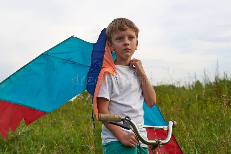 Junge startet in den blauen Himmel einen Drachen stockbilder