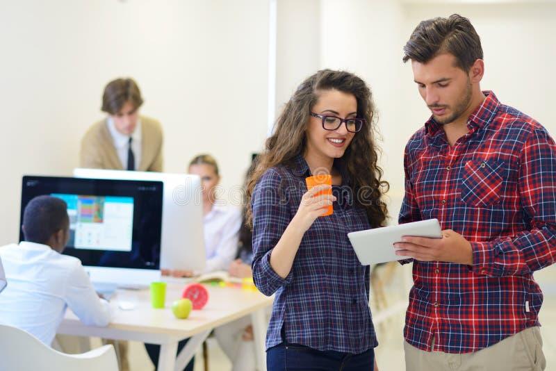 Junge Startgeschäftsleute, Paare, die an Tablet-Computer arbeiten stockbild