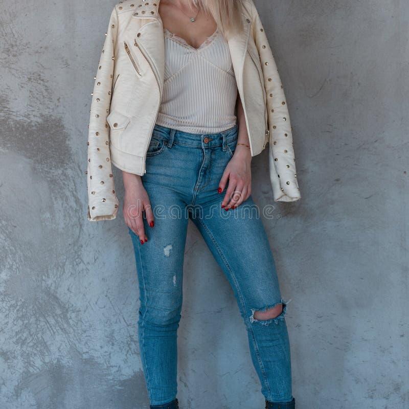 Junge stilvolle Frau in der modernen Kleidung steht nahe der grauen Betonmauer Die Kleidung der Frühlingsart-Frauen stockfoto