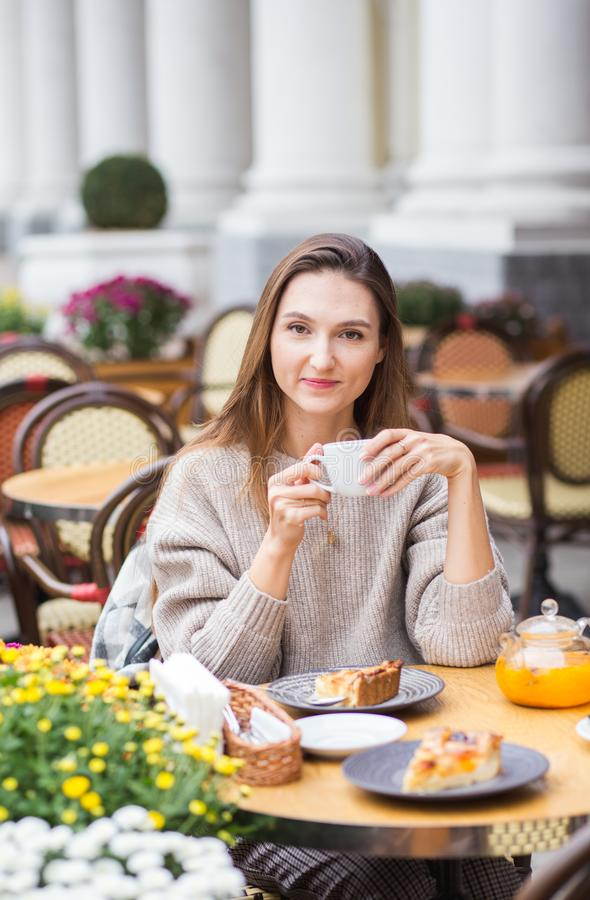 Junge stilvolle Frau, die französisches mit dem Kaffee und Kuchen sitzen an der Caféterrasse frühstückt lizenzfreies stockbild