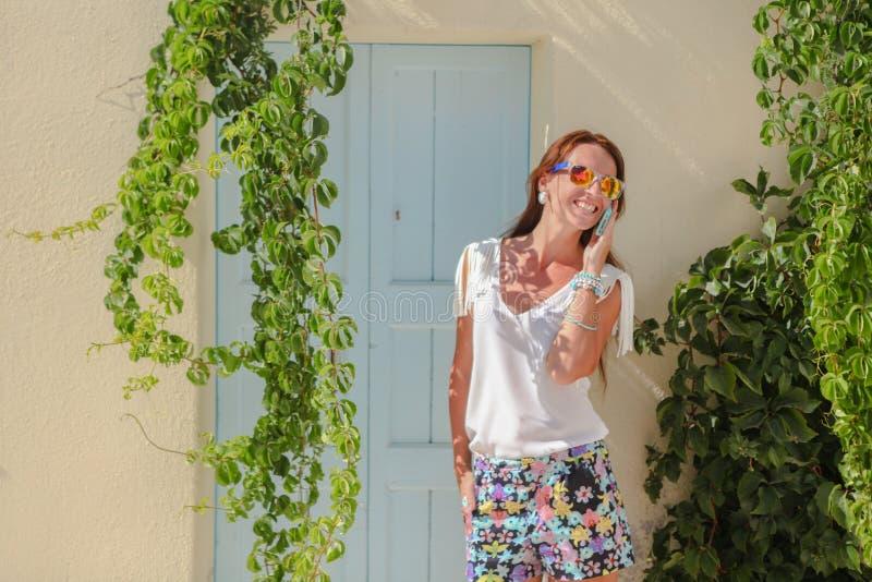 Junge stilvolle Frau, die am Telefon auf den Griechen spricht stockbilder