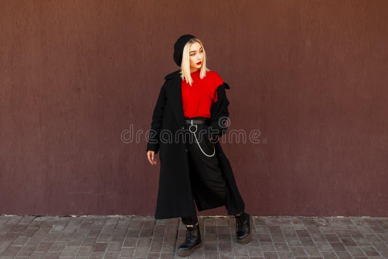 Junge stilvolle Frau in einem schwarzen Herbstmantel mit einem Barett lizenzfreie stockbilder