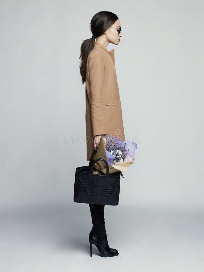 Junge stilvolle Frau im beige Mantel stockfotos