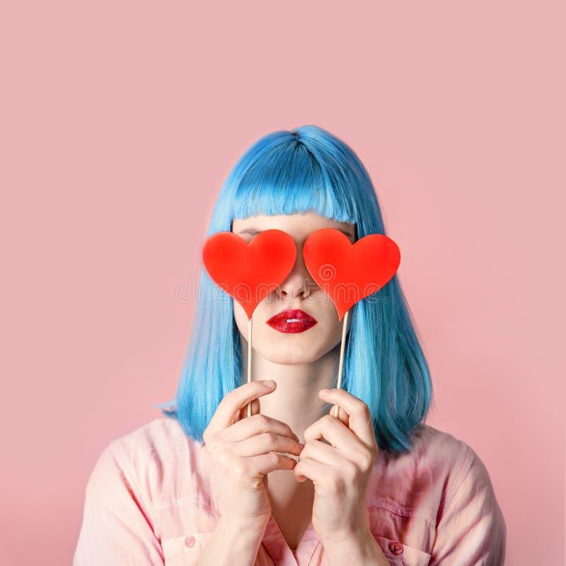 Junge stilvolle Frau mit blauer Frisur und roter Lippenstiftholding lizenzfreies stockbild