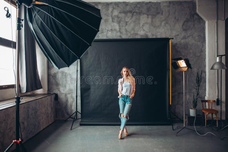 Junge stilvolle Frau mit den gekreuzten Beinen und den Händen auf der Taschenaufstellung lizenzfreie stockfotos