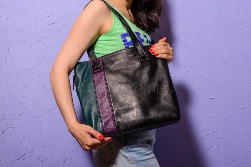 Junge stilvolle Frau mit schwarzer modischer großer Tasche in der Hand lizenzfreie stockfotografie