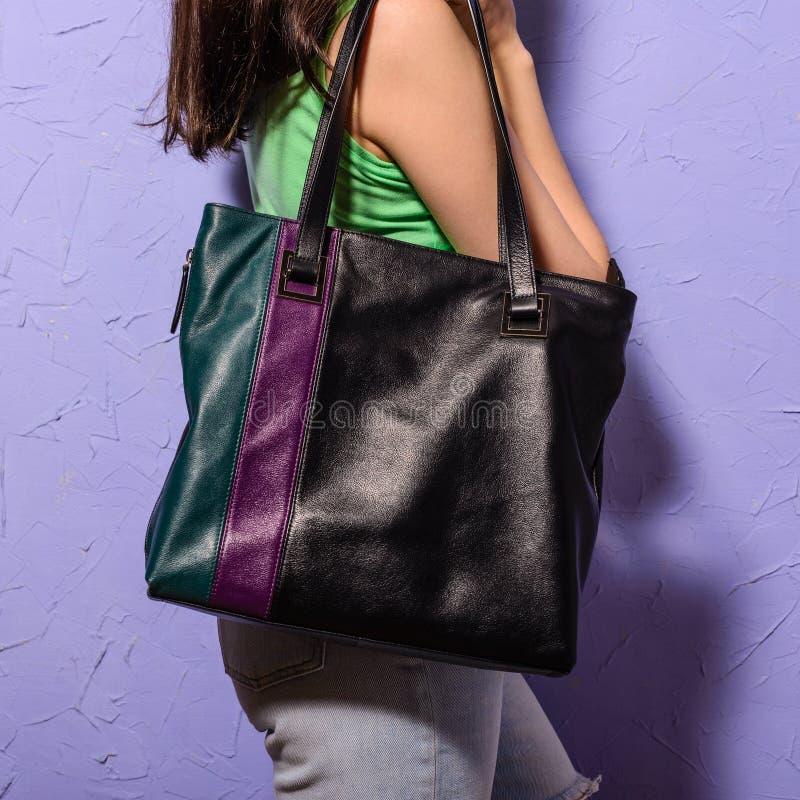 Junge stilvolle Frau mit schwarzer modischer großer Tasche in der Hand lizenzfreies stockbild