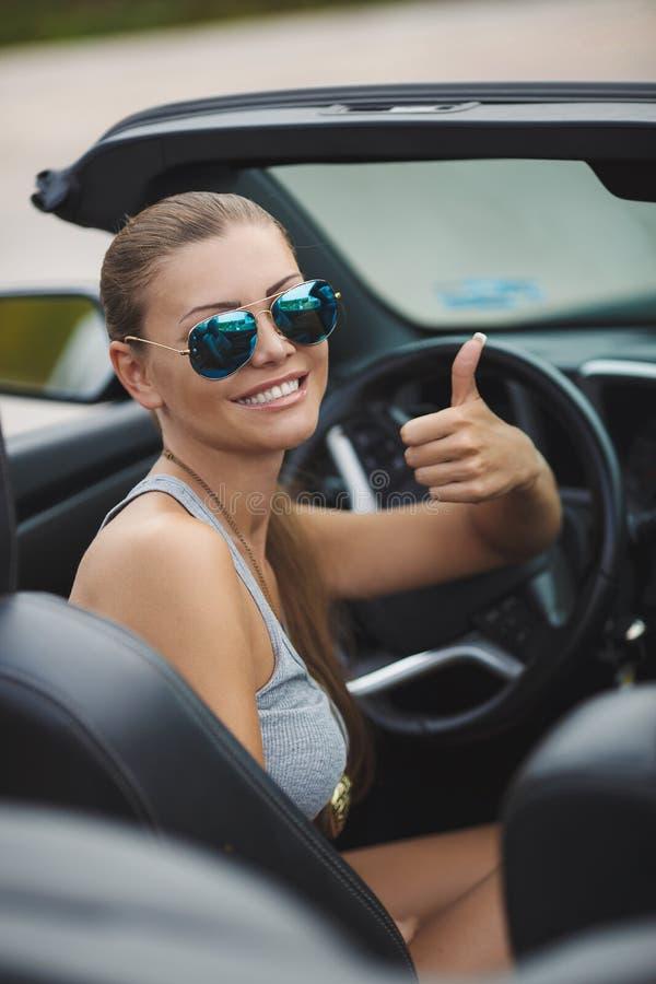 Junge stilvolle Frau reist allein in das Urlaubsgebiet von †‹â€ ‹Europa auf einem schwarzen Cabriolet stockfotografie