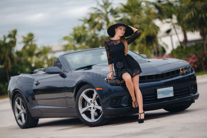 Junge stilvolle Frau reist allein in das Urlaubsgebiet von †‹â€ ‹Europa auf einem schwarzen Cabriolet stockbilder